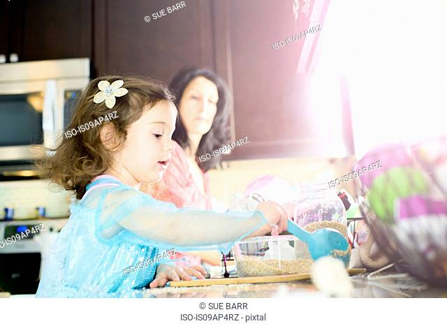 Female toddler and mother baking in kitchen