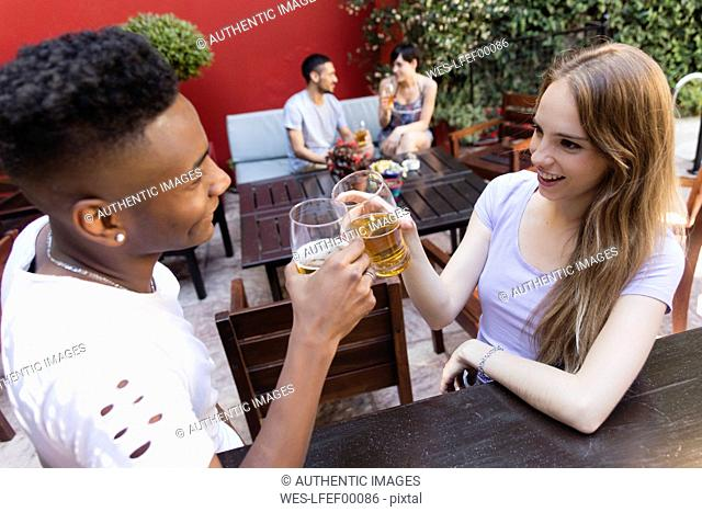 Smiling young couple having a beer at outdoor bar
