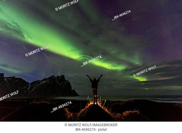 Night shot, man watching Northern Lights (Aurora borealis), Black sand beach, mountains Klifatindur, Eystrahorn and Kambhorn, headland Stokksnes