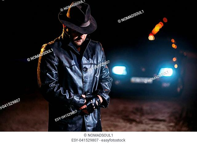 Serial maniac in black leather coat and hat, back view, car light at the night on background. Horror, bloody butcher