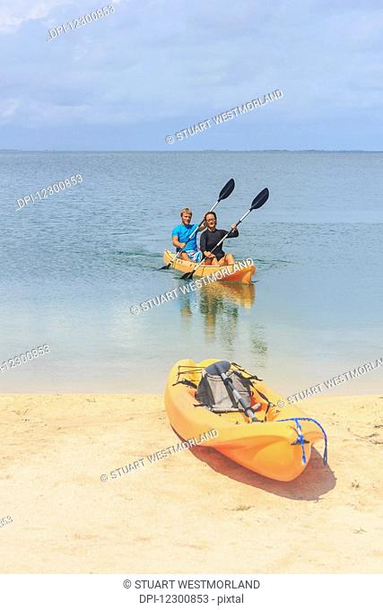 A couple arriving at the beach in a kayak, Saint Georges Caye Resort; Belize City, Belize