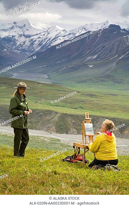 Female National Park Ranger talks with female oil painting artist who is sitting on tundra near Eielson Denali NP Alaska