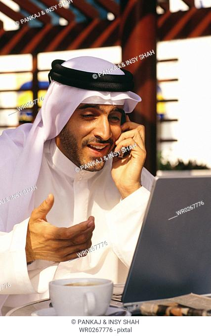 An Arab man smiles as he converses on the mobile phone