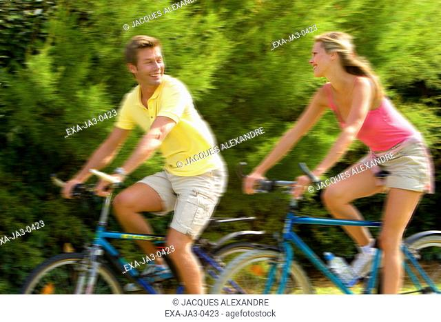 Couple riding bicycles and smiling at each other