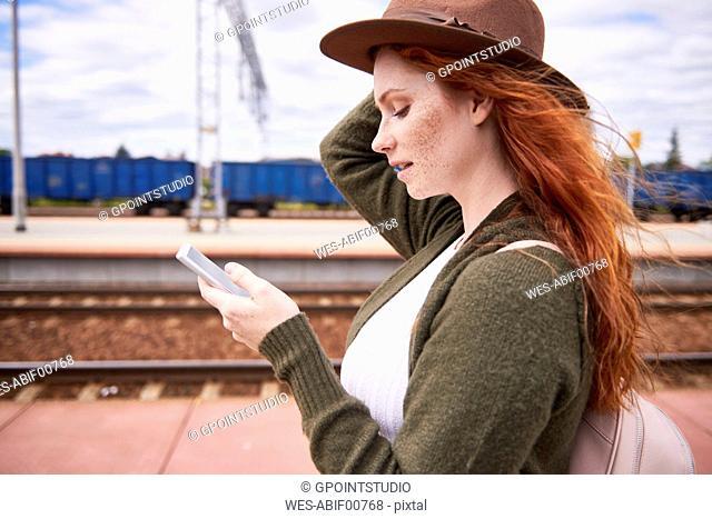 Redheaded woman at platform looking at cell phone