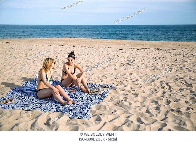 Women relaxing and chatting on beach blanket, Amagansett, New York, USA
