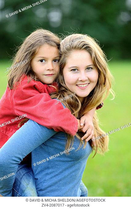 Girl carries her little sister piggyback outdoors, Germany