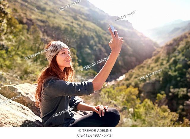 Young woman taking selfie with camera phone on sunny, remote rock