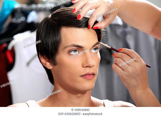 eyebrows with makeup brush, model at mirror in dressing room