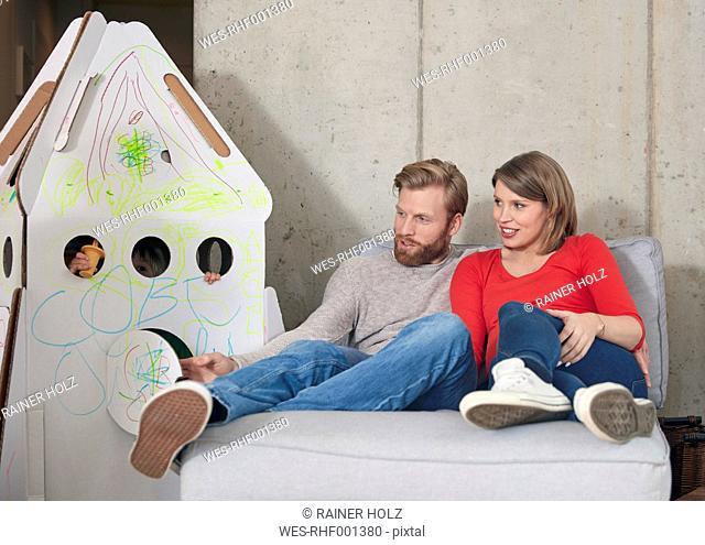 Parents looking at daughter inside cardboard rocket