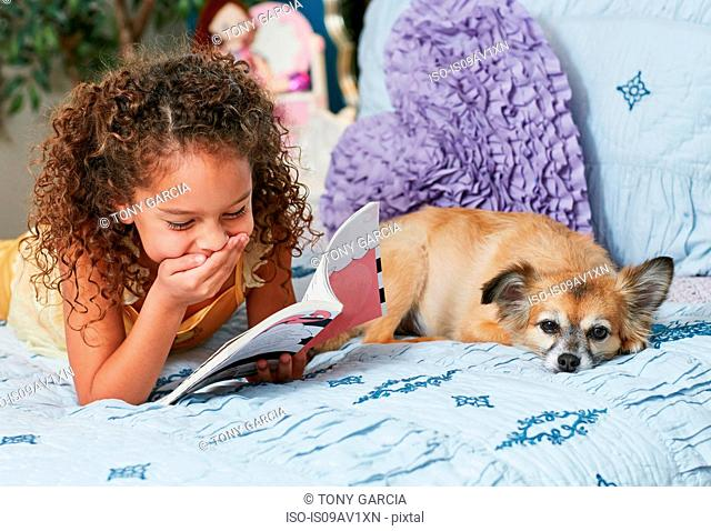 Girl and dog lying on bed reading book, hand on mouth laughing