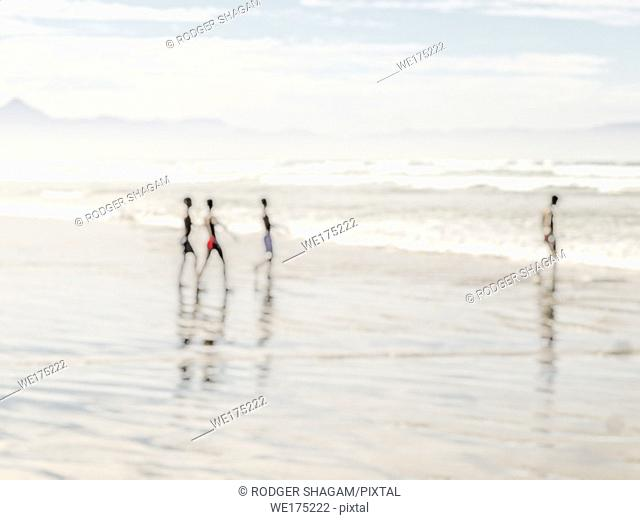 Four young boys having fun during at day at the seaside