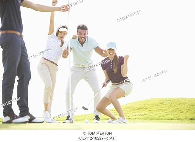 Friends playing golf on course
