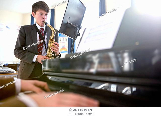 High school student playing saxophone behind music teacher playing piano