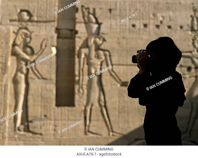 Silhouette of tourist taking pictures in courtyard in front of reliefs