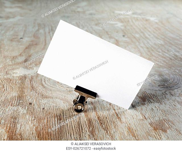 Photo of blank business card with soft shadow on light wooden background. Mock-up for branding identity. Template for graphic designers portfolios