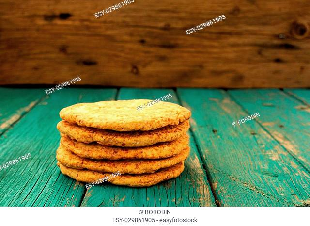 Yummy homemade almond cookies in pile on turquoise shabby background copyspace horizontal
