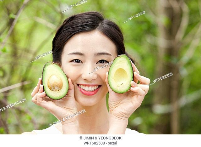 a woman holding an avocado in the nature