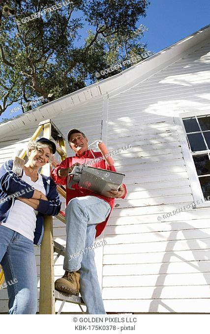 Low angle view of mature couple with ladder and painting tools preparing to paint outside of house