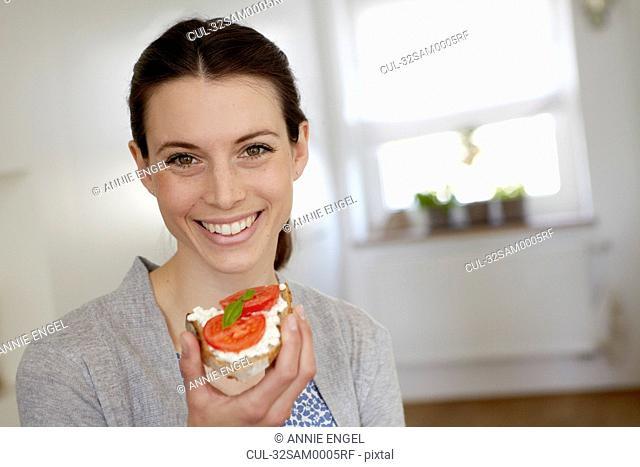 Smiling woman eating tomato sandwich