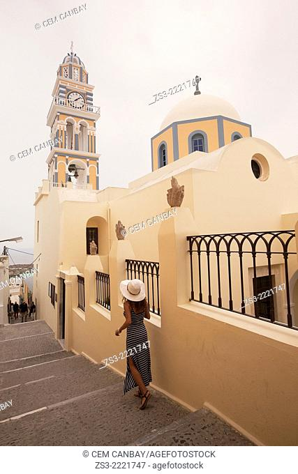 Woman near the Catholic Church of the Sanctus Ioannes Baptista in Fira, Santorini, Cyclades Islands, Greek Islands, Greece, Europe