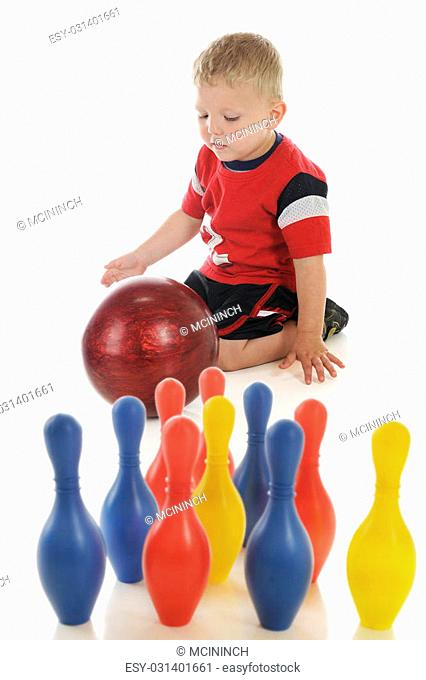 A young preschooler attempting to roll a standard (heavy) bowling ball at his toy, plastic bowling pins. Focus on boy. On a white background