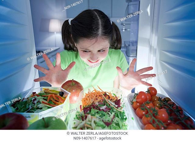 Girl looks in the fridge