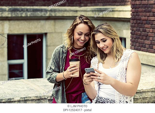 Two female university students standing together on the campus looking at a smart phone; Edmonton, Alberta, Canada