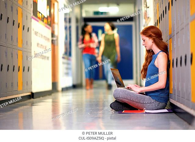 Young female college student sitting on locker room floor typing on laptop