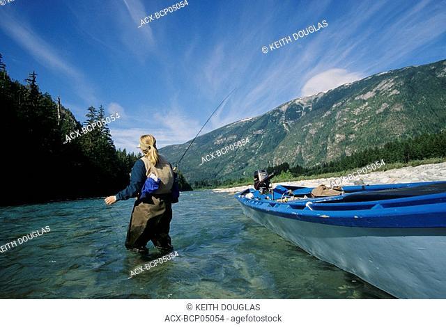 Lady flyfisher fishing for steelhead, Dean river, British Columbia, Canada