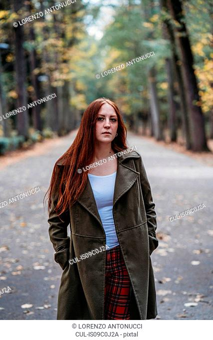 Young woman with long red hair in autumn park, portrait