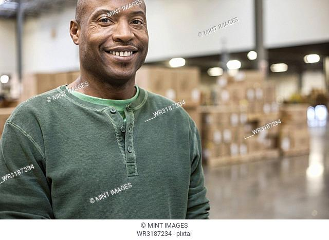 Portrait of an African American warehouse worker in a large distribution warehouse