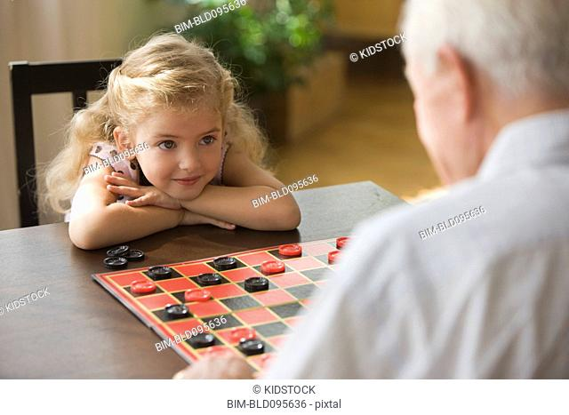 Caucasian grandfather and granddaughter playing checkers