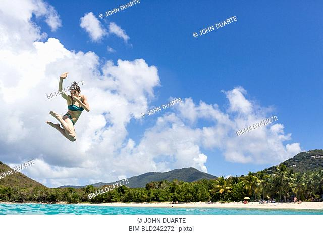 Caucasian woman jumping into tropical ocean