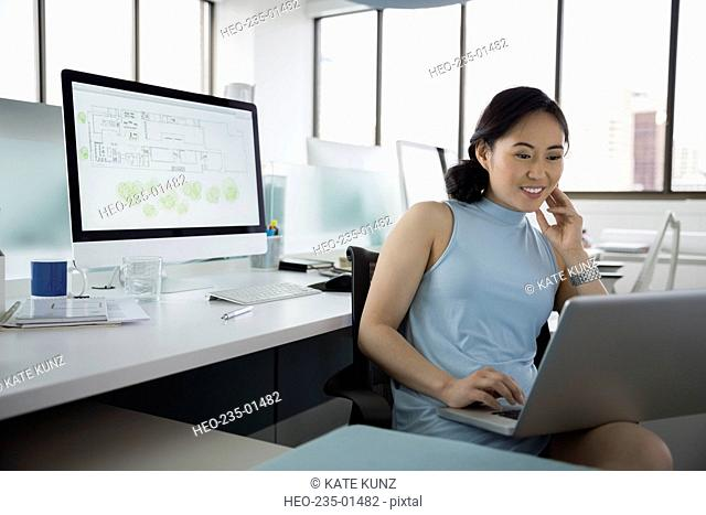 Smiling architect working at laptop in office