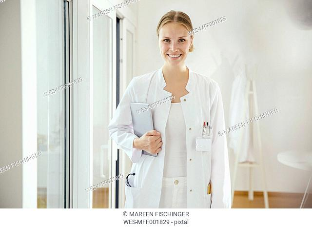 Portrait of smiling female doctor with digital tablet