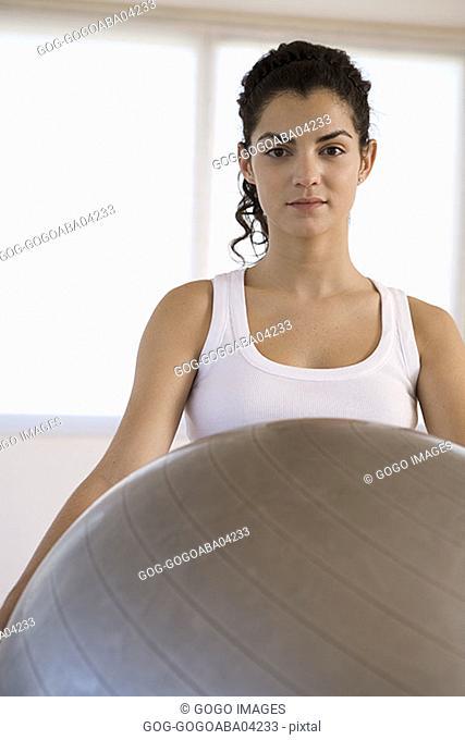 Woman lifting exercise ball
