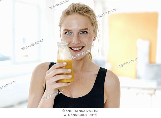 Portrait of smiling young woman in sportswear drinking a smoothie
