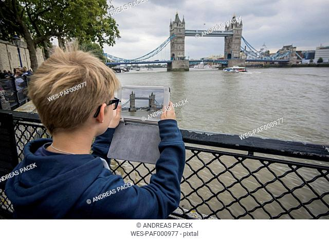 UK, London, boy taking picture with digital tablet at Tower Bridge