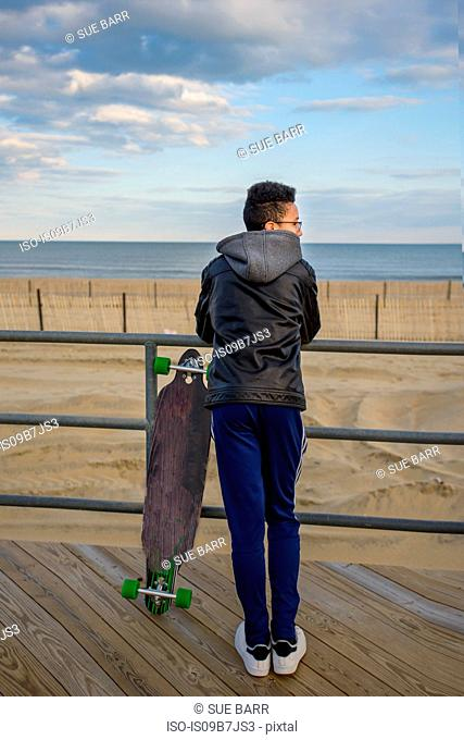 Young boy leaning against railings, looking at view, skateboard beside him, Asbury, New Jersey, USA