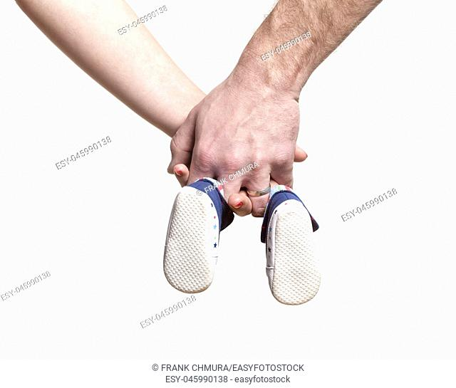 Expecting Couple with Hands Holding Baby Shoes