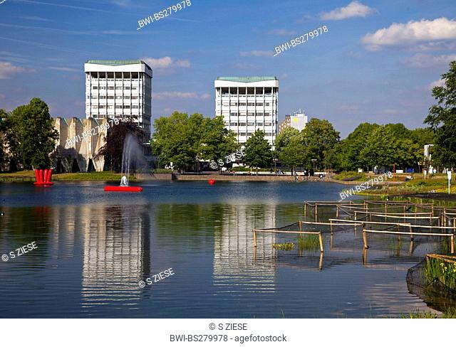 two young people sitting on a bench at the city lake with the two town hall towers in the background reflecting in the water, Germany, North Rhine-Westphalia