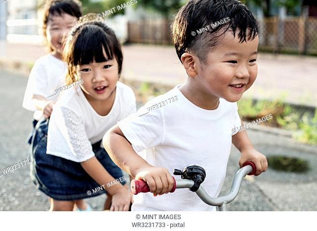Portrait of two Japanese girls and boy playing on street with a bicycle, smiling at camera