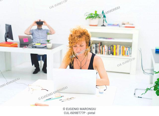 Businesswoman typing on laptop at office desk while listening to headphones