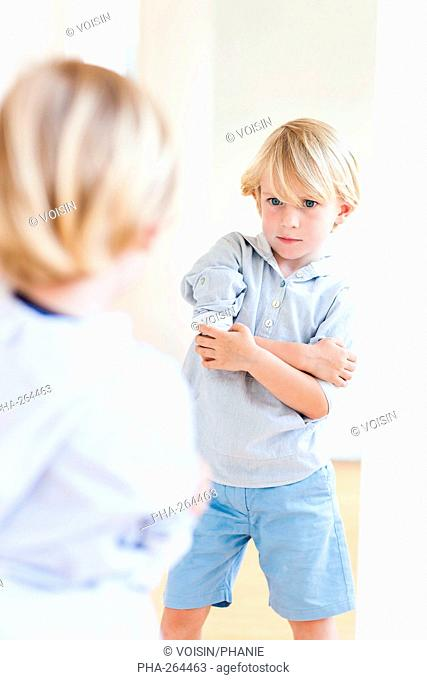 5 year old boy looking in a mirror