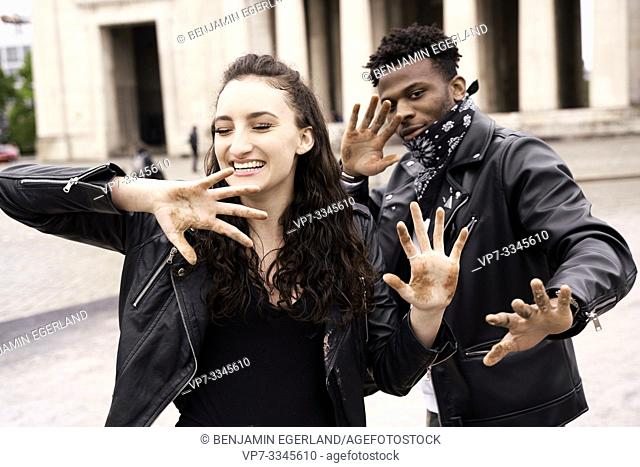 mixed race couple with dirty hands at street in city, in Munich, Germany