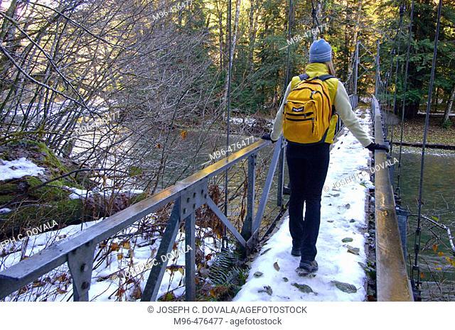 Female hiker on foot bridge over Ohanapecosh River Wash. USA