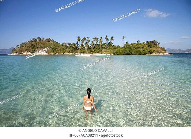 Philippines, El Nido bay,Snake Island,rear view of a woman at sea standing in shallow water