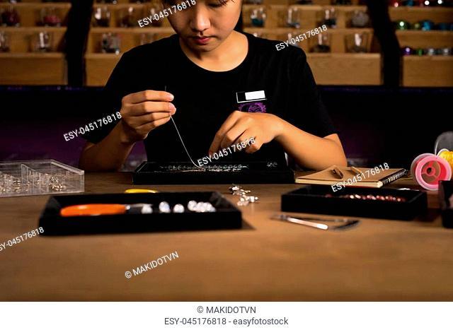 Jeweler making of handmade stone beads jewellery