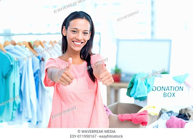Smiling young female volunteer gesturing thumbs up